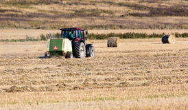 Tractor during harvest. Tractor collecting straws during harvest, two straw rolls on the background and a harvested field in foreground Stock Photos