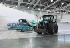 Tractor and harvester are in room at exhibition Royalty Free Stock Image