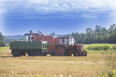 Tractor and harvester working on a sunny august day Stock Photo
