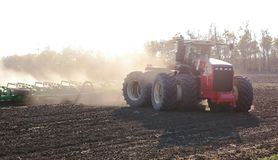 Tractor Harvesting And Soil Cultivation For Subsequent Sowing. Field And Dust In The Sun, Work In Agriculture Stock Photography
