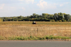 Tractor harvests. Agriculture. The harvest season. Royalty Free Stock Images