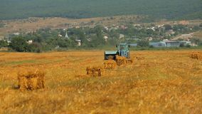 Tractor harvests wheat from the field stock video footage