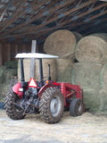 Tractor by the hay bails. A Red tractor parked by the hay bails next to the barn royalty free stock photo