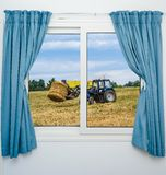 Tractor hay removes the view from the window with curtains Stock Photos