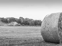 Tractor and Hay Roll in a Field in Black and White Royalty Free Stock Image