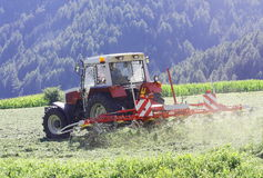 Tractor with hay tedder working on a mountain field.  Royalty Free Stock Image