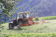 Tractor with hay tedder working on a mountain field Stock Photos