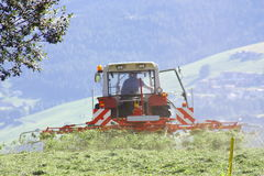 Tractor with hay tedder working on a mountain field.  Stock Photo