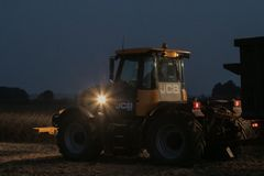 Tractor with headlights on at night time Stock Image