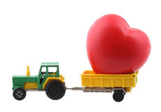 Tractor and heart. Toy tractor with large red heart isolated on white with clipping path Royalty Free Stock Images