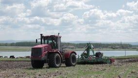 Tractor het drijven op een plattelandsweg op gebied dichtbij een meer stock videobeelden