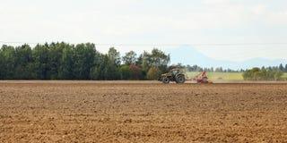 Tractor het zaaien op leeg gebied op platteland met sommige bergen op achtergrond royalty-vrije stock foto