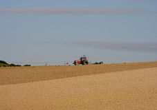 Tractor on Horizon. A tractor ploughing a UK field in the Autumn Stock Photos