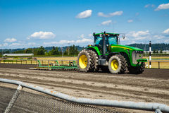 Tractor on horse race track. Horse race track being groomed for the next race by tractor Stock Photos
