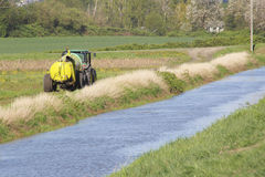 Tractor and Irrigation Water Channel Royalty Free Stock Images