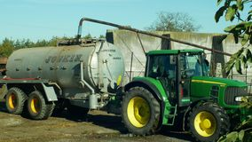 OLOMOUC, CZECH REPUBLIC, OCTOBER 24, 2018: Tractor John Deere special trailer spreading fertilizer of slurry on field. Tractor John Deere special trailer stock video