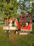 Excavator of red color on a green grass Royalty Free Stock Images