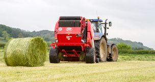 Tractor and lely baler. A modern blue tractor and lely baler making round bales in english crop hay field royalty free stock photos