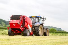 Tractor and lely baler. A modern blue tractor and lely baler making round bales in english crop hay field with jcb loader stock image