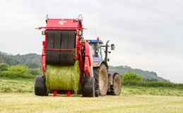 Tractor and lely baler. A modern blue tractor and lely baler making round bales in english crop hay field with jcb loader royalty free stock photos