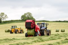 Tractor and lely baler. A modern blue tractor and lely baler making round bales in english crop hay field and jcb loader Stock Photos