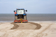 Tractor leveling the beach Royalty Free Stock Photos
