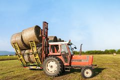 Tractor lifting hay bale on barrow. Agricultural landscape Royalty Free Stock Photos