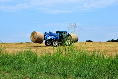 Tractor loading hay bales Royalty Free Stock Images