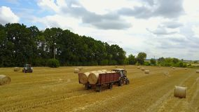 Tractor Loading Hay Bales stock footage