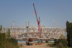 Tractor loads dry branches in the truck on the background construction of a new football stadium `Volgograd-Arena` for the world C. Volgograd, Russia - May 02 stock image