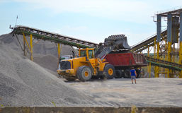 Tractor loads gravel into the car Stock Images