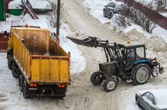 Tractor loads the snow in the truck for snow removal from the city royalty free stock photos