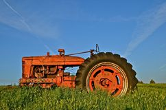 Tractor in Long Grass. An old tractor is parked in the long prairie grass Stock Photos