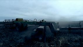 Tractor plows the field with a plow in the evening. Tractor, lowered the plow into the ground and plows the field after sunset stock video footage