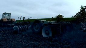 The tractor lowers the plow into the ground and begins plowing after sunset. The tractor, with the plow trailer, lowers the plow into the ground and begins stock video footage
