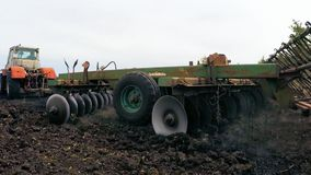Tractor lowers the plow mill into the ground for field arable land. The tractor lowers the millstone of the plow into the ground for arable land of a wheat field stock video footage