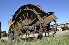 Tractor with lugs on wheels. An old yellow tractor in a junkyard with steel wheels and lugs for greater traction Royalty Free Stock Photos