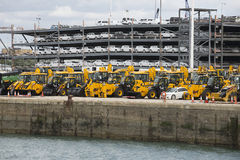 Tractor and luxury cars await export from docks UK Royalty Free Stock Images