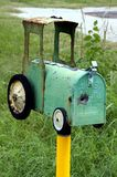 Tractor Mailbox with Bullet Hole. A rural or country mailbox shaped like a tractor with a bullet hole in the front in the vertical or portrait view Royalty Free Stock Photography