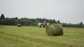 Tractor make straw bale. Agriculture tractor machine make press straw hay bales in autumn field circa June 2013 in Zibalai, Lithuania stock footage