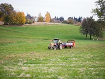 The tractor with the manure spreader working in the field royalty free stock image