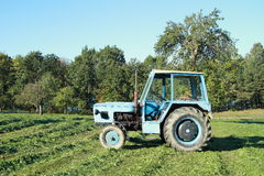 Tractor on the meadow. An old blue tractor vehicle standing on the meadow stock photography