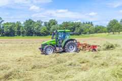 Tractor in meadow making hay Royalty Free Stock Photos