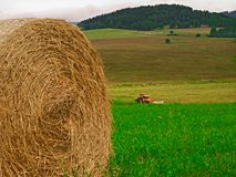 Tractor on a meadow with straw bales. Tractor working on the field and in the foreground is a bundle of straw Stock Photography
