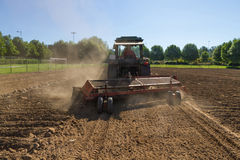 Tractor Mechanical Rake to Gather Stones of the the Land. Tractor rake cleaner stones land. In this case the construction of a football field royalty free stock image