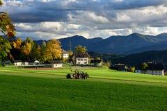 Tractor met een baalomslag die een hooibaal voorbereidingen treffen te verpakken Dorp Obermillstatt, Carinthia, Oostenrijk stock foto's