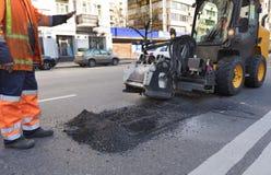 Tractor met een pijp voor reparatie van schade op asfalt stock fotografie