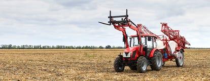 Tractor met een spuitbus voor landbouwchemie met een gebied stock foto's