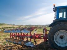 Tractor met ploeg Stock Afbeelding