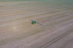 Tractor met scharnierend systeem om pesticiden te bespuiten Bevruchtend met een tractor, in de vorm van een aërosol, op het gebie royalty-vrije stock foto